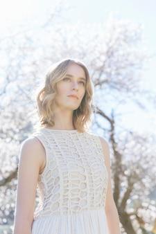 Vista de ángulo bajo mujer en blanco bajo la luz solar