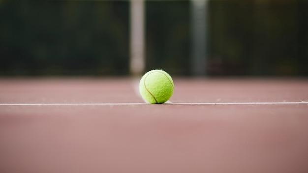 Vista de ángulo bajo con pelota de tenis en campo