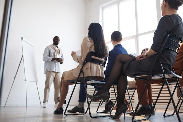 Vista de ángulo bajo a personas que escuchan al entrenador de negocios mientras están sentados en sillas en la audiencia en una conferencia o seminario, destello de lente, espacio de copia
