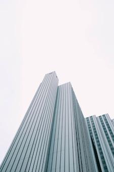 Vista de ángulo bajo de un rascacielos moderno con ventanas azules y blancas bajo un cielo blanco