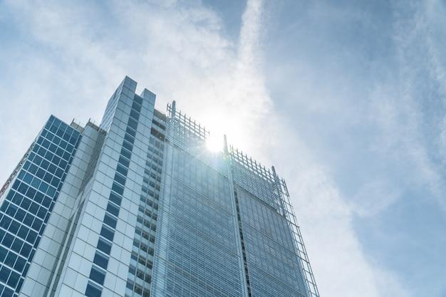 Vista de ángulo bajo de un rascacielos con sol y nubes