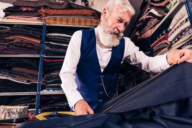 Vista de ángulo bajo del sastre masculino mayor que toma la medida de tela azul con cinta métrica