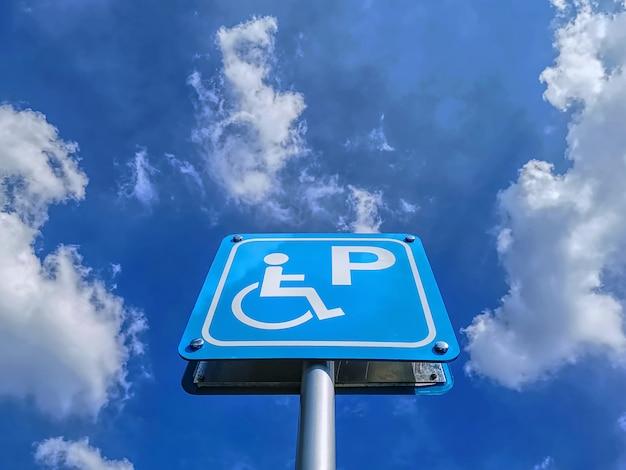 Vista de ángulo bajo de la señal azul de estacionamiento para discapacitados contra el cielo azul nublado durante el día