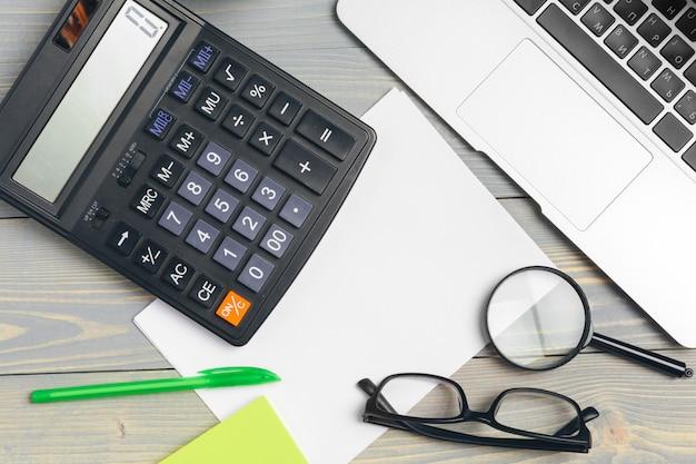 Vista en ángulo del teclado de la computadora portátil y gafas con diversos suministros de oficina en escritorio de madera