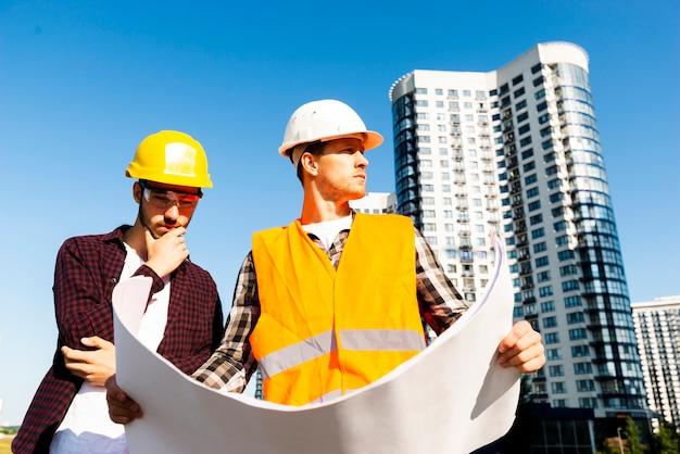 Vista de ángulo bajo de tiro medio de ingeniero y arquitecto mirando planes