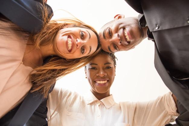 Vista de ángulo bajo de tres colegas multiétnicos felices abrazando