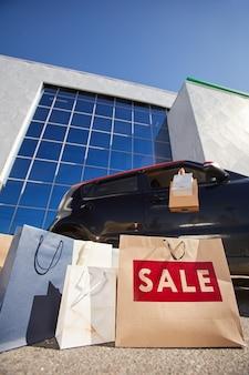 Vista de ángulo bajo vertical en bolsas de la compra con cartel de venta al aire libre contra el edificio del centro comercial y el coche en la superficie, espacio de copia