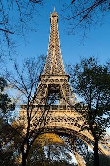 Vista de ángulo bajo vertical de la torre eiffel bajo la luz del sol durante el día en parís en francia Foto gratis
