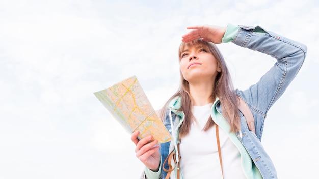Vista de ángulo bajo de un viajero femenino que protege sus ojos contra el cielo