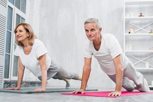 Vista de ángulo bajo de los viejos pares haciendo flexiones de brazos en la estera en casa