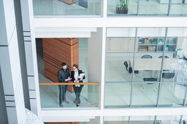 Vista anterior de los analistas de negocios jóvenes modernos de pie en la barandilla vidriosa y discutiendo el informe con tableta