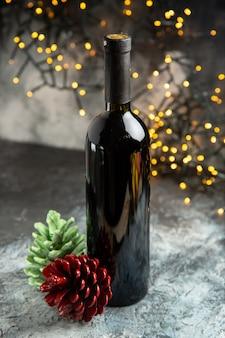 Vista anterior de la botella de vino tinto para la celebración y dos conos de coníferas sobre fondo oscuro