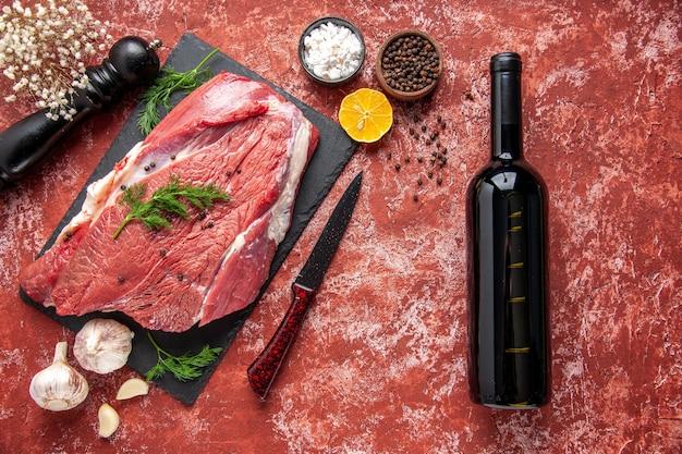 Vista anterior de carne roja fresca cruda con verde y pimienta en tablero negro, cuchillo, ajo, especias de limón, martillo de madera, botella de vino de limón sobre fondo rojo pastel de aceite