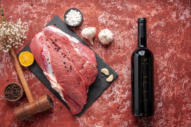 Vista anterior de carne roja fresca con pimienta en tablero negro cuchillo ajos especias de limón martillo de madera marrón botella de vino de limón sobre fondo rojo pastel de aceite