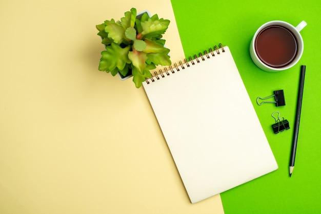 Vista anterior del cuaderno blanco con bolígrafo junto a una taza de té maceta sobre fondo blanco y amarillo
