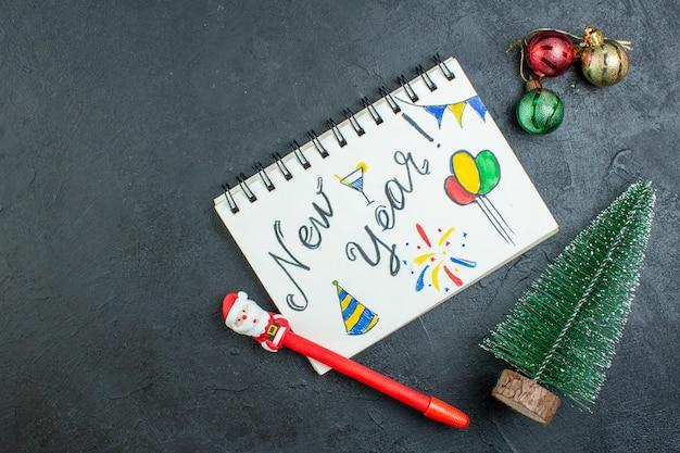 Vista anterior del cuaderno de espiral con escritura de año nuevo y bolígrafo junto a los accesorios de decoración del árbol de navidad sobre fondo oscuro
