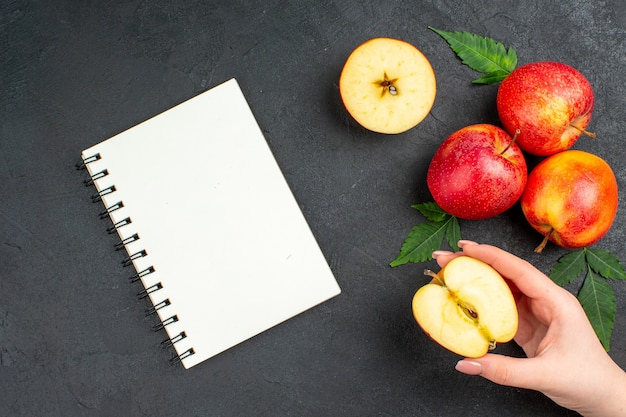 Vista anterior del cuaderno y manzanas rojas frescas cortadas enteras y hojas sobre fondo negro