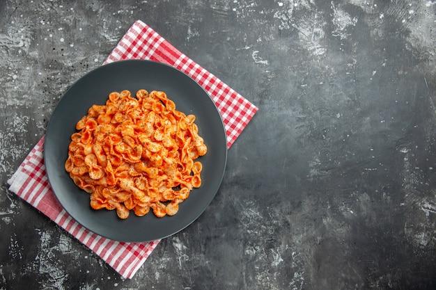 Vista anterior de la deliciosa comida de pasta en una placa negra para cenar sobre un paño rojo despojado