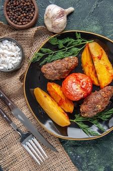 Vista anterior de deliciosas chuletas de carne al horno con patatas y tomates en una placa negra, especias, ajos, cubiertos en verde negro mezcla de colores de fondo