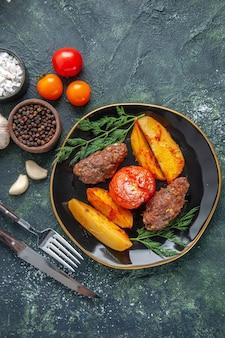 Vista anterior de deliciosas chuletas de carne al horno con patatas y tomates en un plato negro cubiertos juego especias ajo tomates