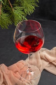 Vista anterior de delicioso vino tinto en una copa de cristal sobre una toalla y ramas de abeto sobre un fondo oscuro
