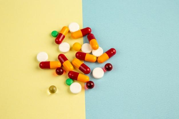 Vista anterior de diferentes píldoras en la superficie azul amarillo color pandémico hospital covid- ciencia laboratorio de medicamentos de virus de salud