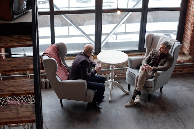 Vista anterior de elegantes hombres de negocios de mediana edad sentados en cómodos sillones y bebiendo alcohol en el bar del vestíbulo