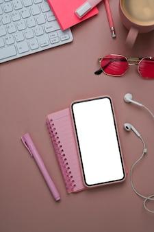 Vista anterior del espacio de trabajo femenino con teléfono inteligente, auricular, portátil y teclado sobre fondo rosa pastel.