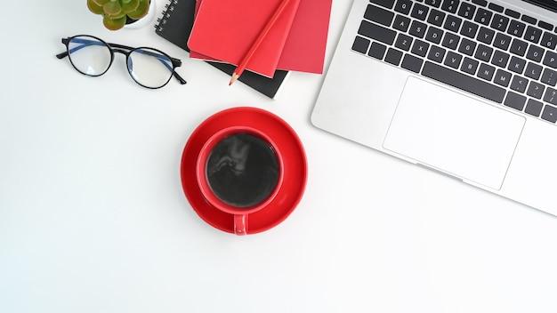 Vista anterior del espacio de trabajo moderno con computadora portátil, taza de café, cuaderno y vasos en la mesa blanca.