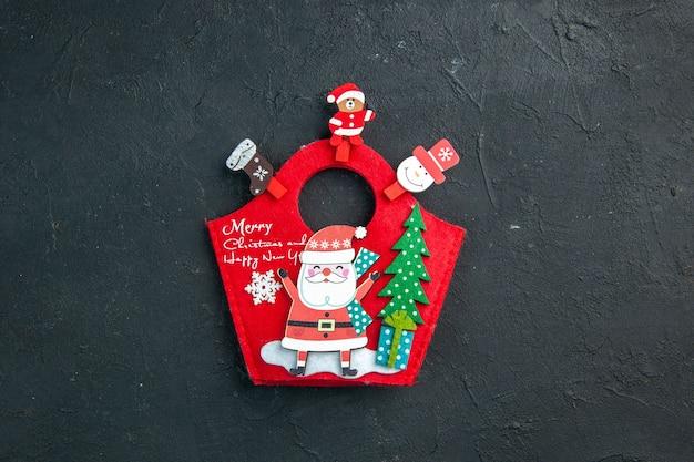 Vista anterior del estado de ánimo navideño con accesorios de decoración y caja de regalo de año nuevo en una superficie oscura