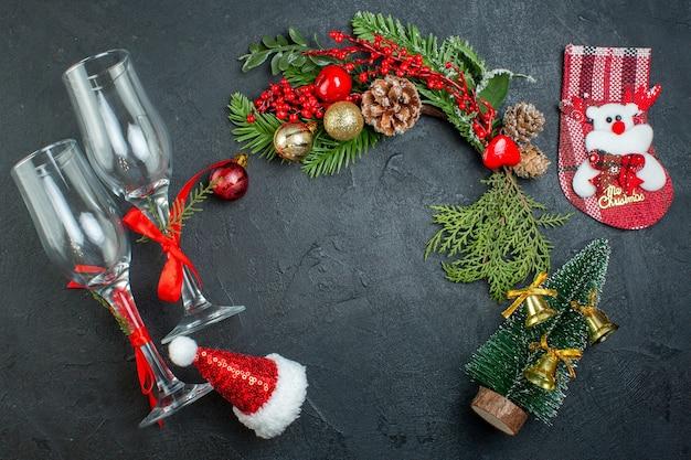 Vista anterior del estado de ánimo navideño con copas de cristal caído ramas de abeto calcetín de árbol de navidad sombrero de santa claus sobre fondo oscuro