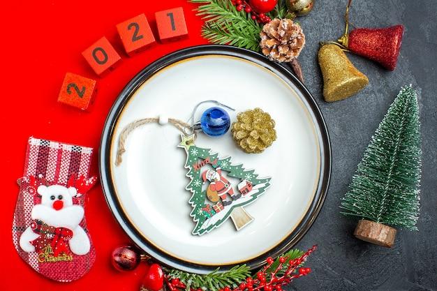 Vista anterior del fondo de año nuevo con accesorios de decoración de plato de cena ramas de abeto y números calcetín de navidad en una servilleta roja junto al árbol de navidad en una mesa negra