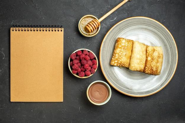 Vista anterior del fondo de la cena con deliciosos panqueques de miel y chocolate y frambuesa junto al cuaderno sobre fondo negro