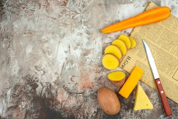 Vista anterior de fondo de cocción con diversas verduras y dos tipos de cuchillo de queso en un periódico viejo sobre fondo de color mixto