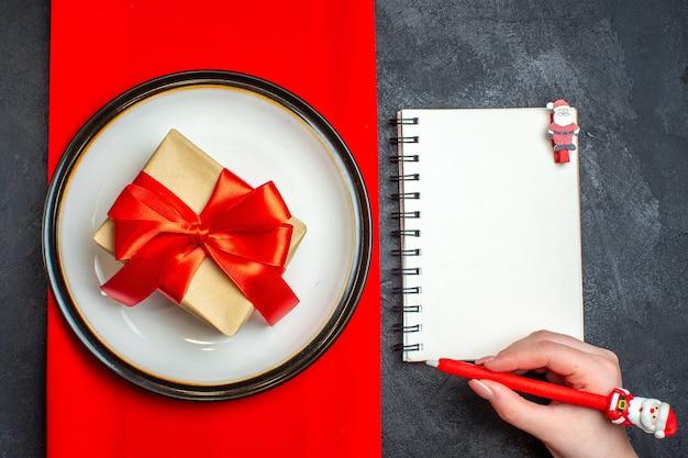 Vista anterior del fondo de comida cristiana nacional con regalo con cinta roja en forma de arco en platos vacíos en una servilleta roja y mano sosteniendo un bolígrafo en el cuaderno sobre fondo negro