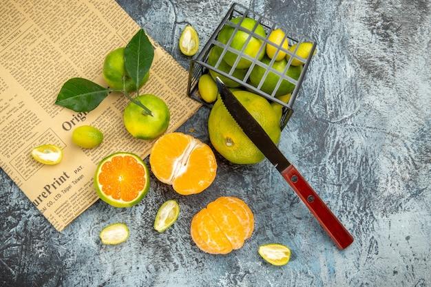 Vista anterior de frutas cítricas frescas con hojas caídas de una canasta negra cortada por la mitad y un cuchillo en un periódico sobre fondo gris
