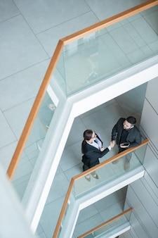 Vista anterior de la gente de negocios de pie en el balcón y haciendo apretón de manos después de la negociación