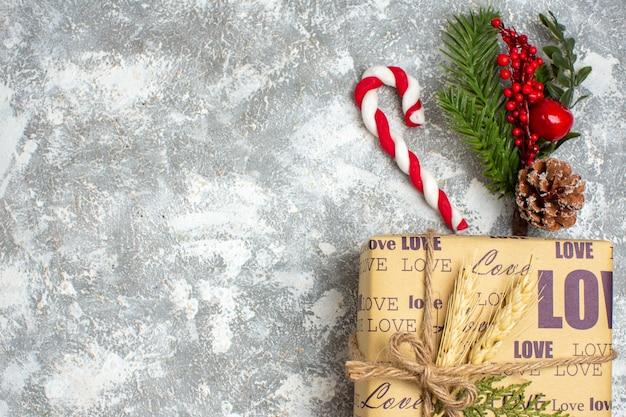 Vista anterior del hermoso regalo lleno de navidad con inscripción de amor y accesorios de decoración de ramas de abeto, cono de coníferas en el lado izquierdo sobre la superficie del hielo