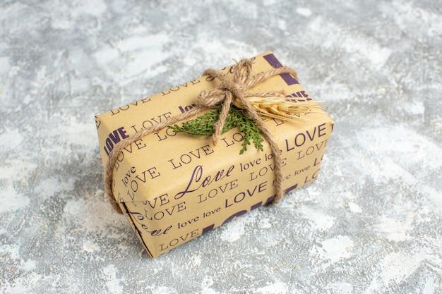 Vista anterior del hermoso regalo lleno de navidad con inscripción de amor en la mesa de hielo