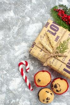 Vista anterior del hermoso regalo lleno de navidad con inscripción de amor pequeños cupcakes dulces y accesorios de decoración de ramas de abeto cono de coníferas en la superficie del hielo