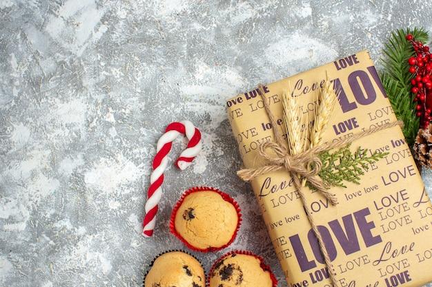 Vista anterior del hermoso regalo lleno de navidad con inscripción de amor, pequeños cupcakes, dulces y ramas de abeto, accesorios de decoración, cono de coníferas en el lado izquierdo sobre la superficie del hielo