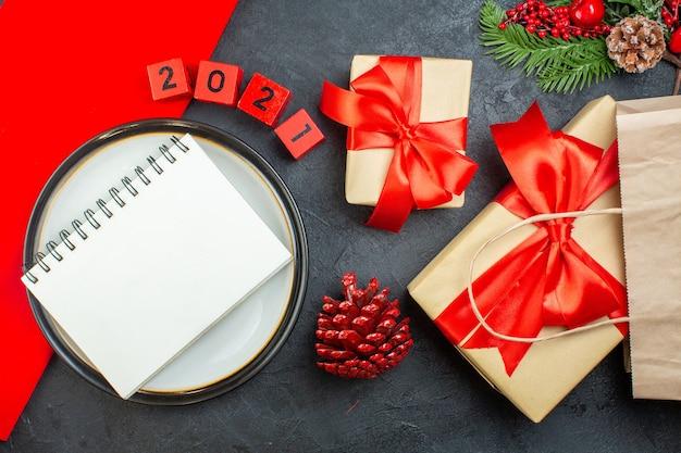 Vista anterior de hermosos regalos y cuaderno en una placa conífera cono números de ramas de abeto sobre una mesa oscura