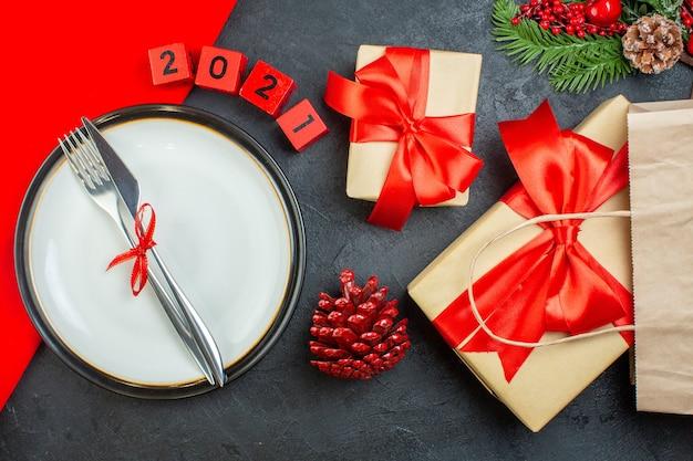 Vista anterior de hermosos regalos y cubiertos en un plato de coníferas números de ramas de abeto de cono sobre un fondo oscuro