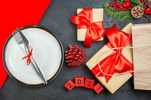 Vista anterior de hermosos regalos y cubiertos en un plato de coníferas números de ramas de abeto de cono sobre una mesa oscura