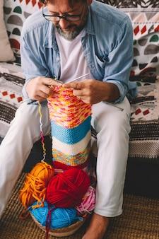 Vista anterior del hombre y la actividad hobby interior de tejer el trabajo con lana de colores. actividad de ocio en casa para personas en temporada de invierno. pasatiempo relajado cómodo en el sofá