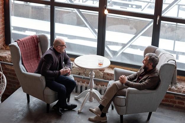 Vista anterior de hombres de mediana edad ricos positivos charlando y bebiendo whisky en un pub de lujo
