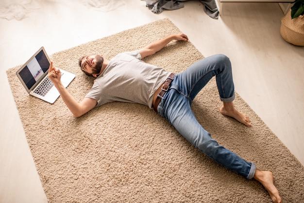 Vista anterior de un joven agotado en jeans acostado sobre una alfombra en la sala de estar y dando vueltas al entrenador en clase en línea
