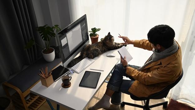 Vista anterior del joven diseñador gráfico que trabaja con una computadora moderna y juega a su gato en la oficina en casa.