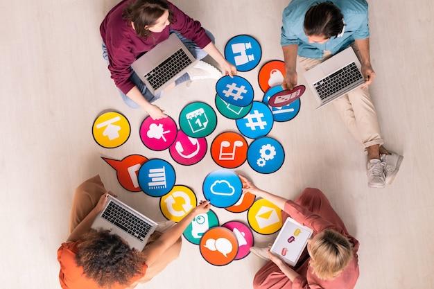 Vista anterior de jóvenes especialistas en marketing de redes sociales sentados en el piso y usando computadoras mientras analizan herramientas de marketing