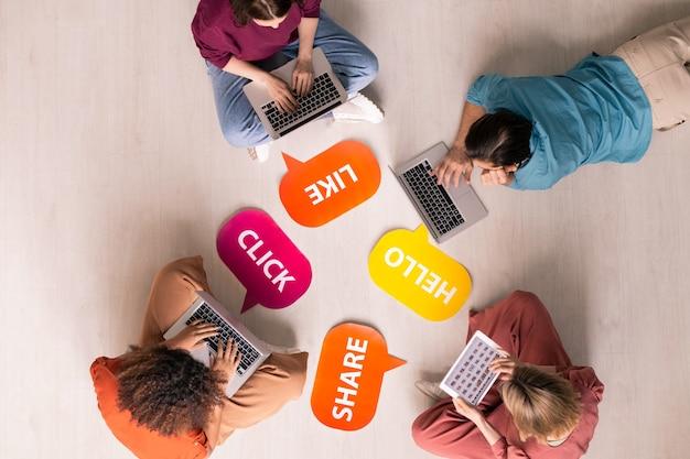 Vista anterior de jóvenes sentados y acostados en el suelo con etiquetas de actividad de internet y que utilizan dispositivos portátiles modernos, concepto de adicción a las redes sociales